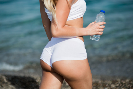 Beautiful young woman with long blond hair in white shorts is standing a back on the coastline of the sea Stok Fotoğraf