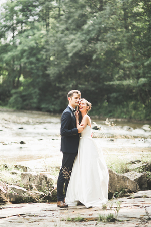 village man: Beautifull wedding couple kissing and embracing near the shore of a mountain river with stones
