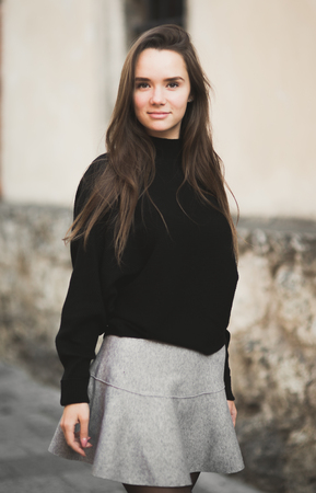 Fashion woman portrait of young pretty trendy girl posing at the city in Europe
