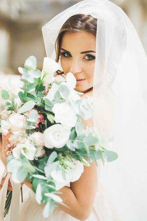 Wonderful bride with a luxurious white dress and bouquet