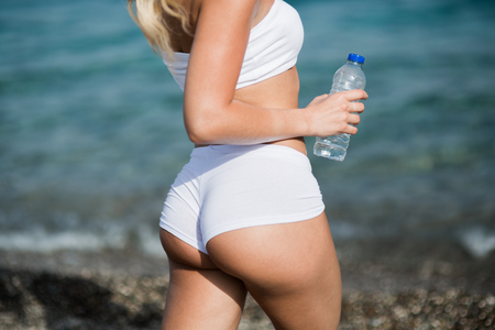 Beautiful young woman with long blond hair in white shorts is standing a back on the coastline of the sea Foto de archivo