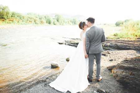 Bride and groom holding beautiful wedding bouquet. Posing near river Imagens - 90453773