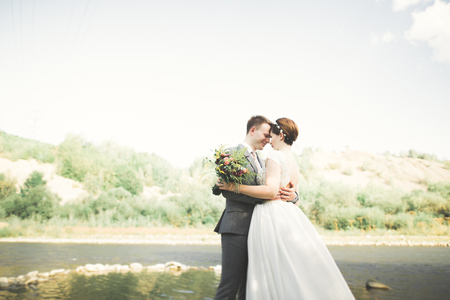 Bride and groom holding beautiful wedding bouquet. Posing near river Archivio Fotografico - 90500765