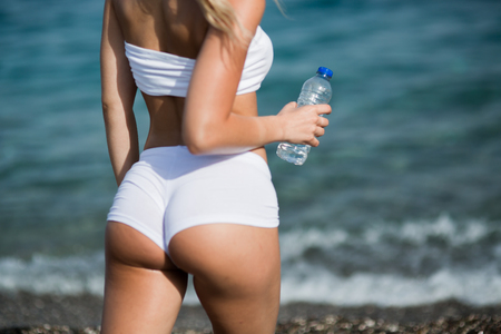 Beautiful young woman with long blond hair in white shorts is standing a back on the coastline of the sea 스톡 콘텐츠