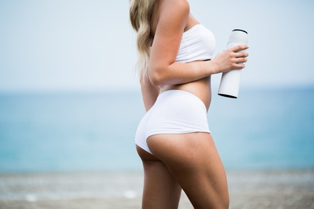 Beautiful young woman with long blond hair in white shorts is standing a back on the coastline of the sea Stock Photo