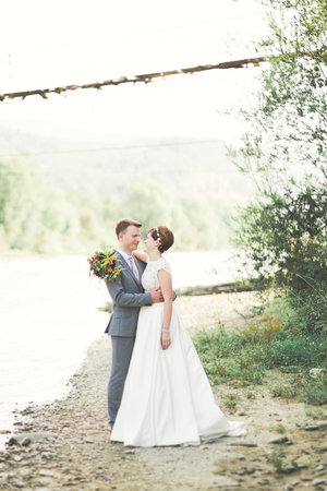 Bride and groom holding beautiful wedding bouquet. Posing near river Imagens