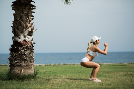 beautiful girl is working out in summer park with a view on the sea