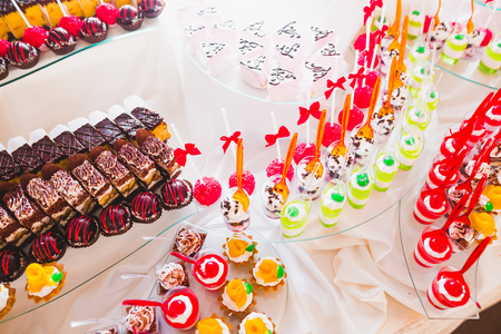 Delicious sweets on wedding candy buffet with desserts, cupcakes Stock Photo - 92805735