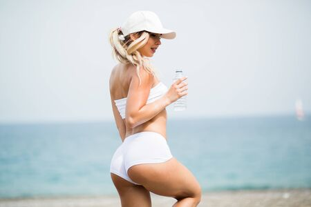 Fitness beautiful woman is drinking water after exercising on summer hot day in beach. Female athlete after work out Stock Photo