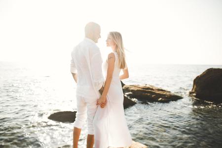 Romantic loving couple posing on stones near sea, blue sky Stock Photo