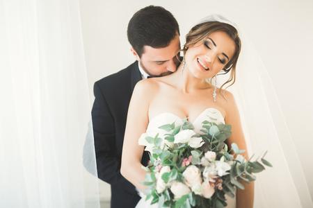 Wedding photo shoot of the newlyweds couple in a beautiful hotel posing near window Stock Photo
