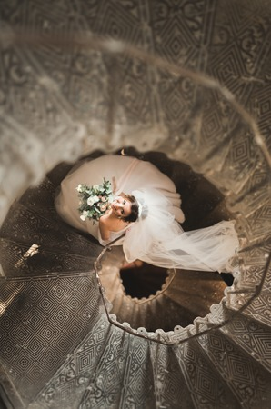 Beautiful bride in magnificent dress stands alone on stairs Stock Photo