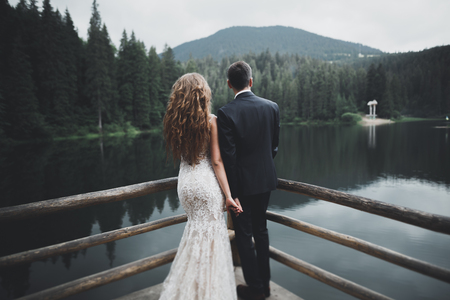 Young newly wed couple, bride and groom kissing, hugging on perfect view of mountains, blue sky Stock Photo