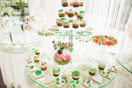 Delicious sweets on wedding candy buffet with desserts, cupcakes Stock Photo - 94623960