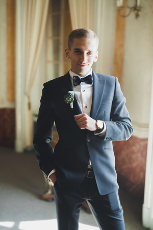 Happy handsome smiling groom posing with boutonniere