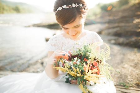 Pretty lady, bride in a wedding dress posing near river Stock Photo
