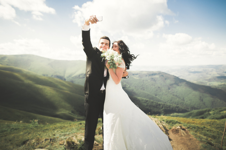 Just married couple on top of the mountain taking selfie picture Фото со стока