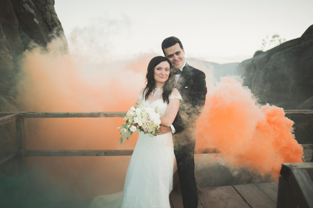 Wedding couple posing near rocks with colored smoke behind them