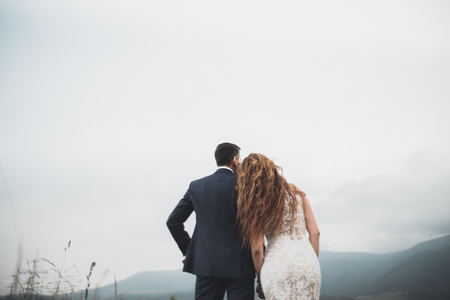 Beautiful gorgeous bride posing to groom and having fun, luxury ceremony at mountains with amazing view, space for text, wedding couple