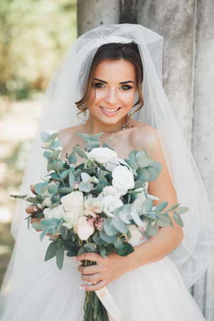 Beautiful brunette bride in elegant white dress holding bouquet posing neat trees