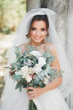Mooie donkerbruine bruid in het elegante witte boeket die van de kledingsholding keurige bomen stellen
