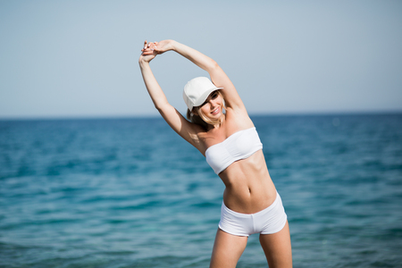 Slim female girl with beautiful figure is doing stretching exercise on the beach, morning run, fitness and healthy lifestyle concept Stock Photo
