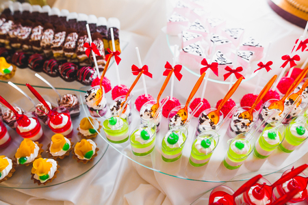 Delicious sweets on wedding candy buffet with desserts, cupcakes Stock Photo - 98683768