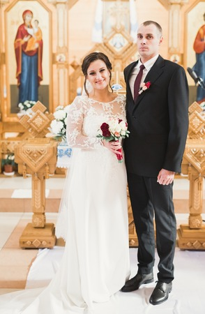 Married couple posing in a church after ceremony