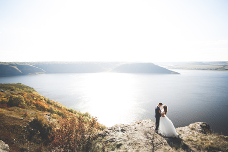 Happy wedding couple staying over beautiful landscape