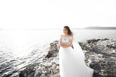 Romantic beautiful bride in white dress posing on the background sea Stock Photo
