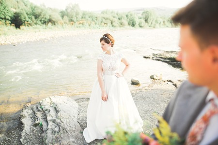 Bride and groom holding beautiful wedding bouquet. Posing near river Archivio Fotografico - 99789391