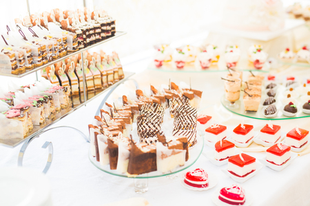 Delicious and tasty dessert table with cupcakes shots at reception closeup