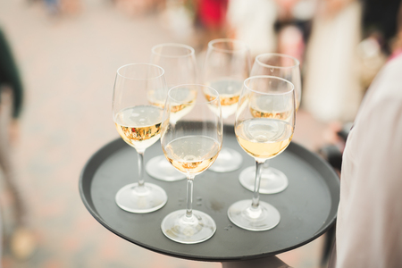 Waiter serving glasses with champagne on a tray Stock Photo