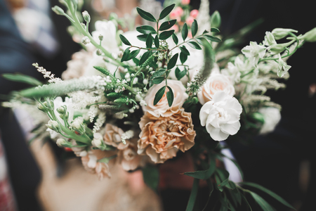 Beauty wedding bouquet with different flowers in hands