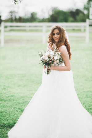 Beautiful bride posing in wedding dress outdoors Stock Photo