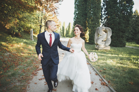 Stylish couple of happy newlyweds walking in the park on their wedding day with bouquet Stock Photo