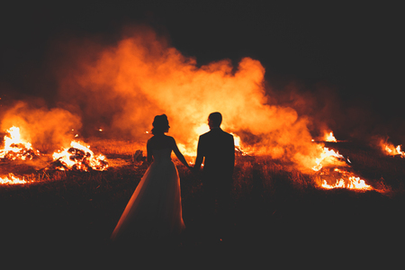 Amazing wedding couple near the fire at night