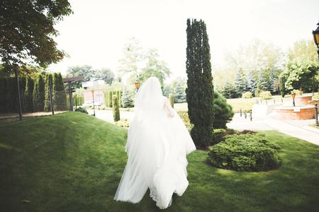 Beautiful bride in elegant white dress holding bouquet posing in park Фото со стока