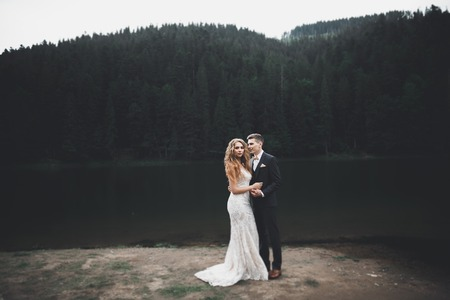 Young newly wed couple, bride and groom kissing, hugging on perfect view of mountains, blue sky Reklamní fotografie