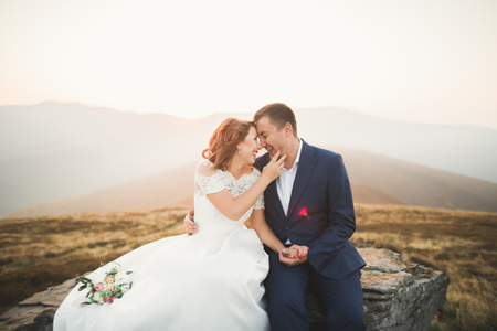 Wedding couple posing on sunset at wedding day. Bride and groom in love Stock Photo