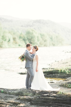 Bride and groom holding beautiful wedding bouquet. Posing near river Archivio Fotografico - 104742176