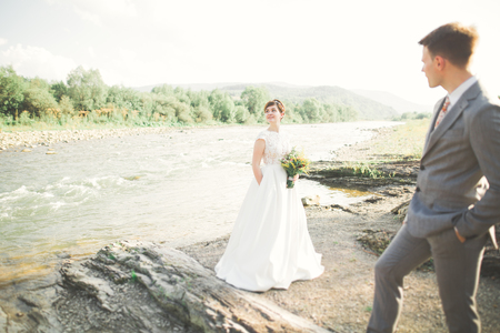 Bride and groom holding beautiful wedding bouquet. Posing near river Imagens - 104742204