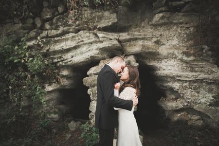 Beautiful romantic wedding couple of newlyweds hugging in park on sunset Stock Photo