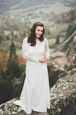Beautiful happy bride outdoors in a forest with rocks. Wedding perfect day