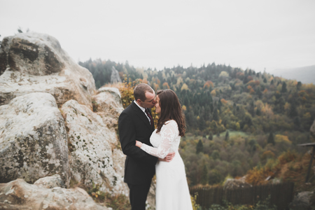 Wedding couple in love kissing and hugging near rocks on beautiful landscape Stock Photo