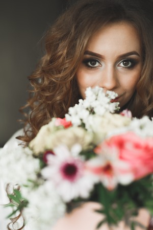 Portrait of beautiful bride with fashion veil at wedding morning. Wedding dress.