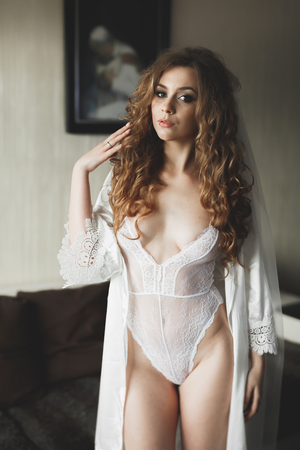 Gorgeous bride in robe posing and preparing for the wedding ceremony face in a room Stock Photo