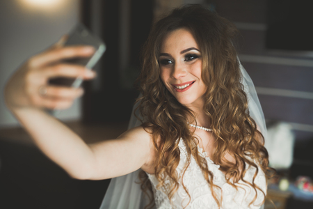 Happy bride taking selfie at home in her wedding day Stock Photo