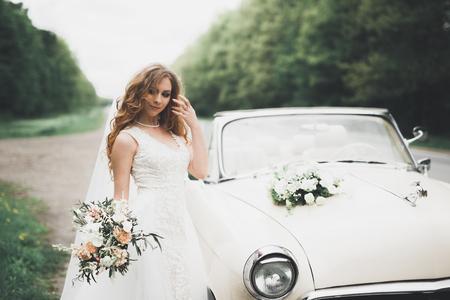 A beautiful bride posing near retro car outdoors