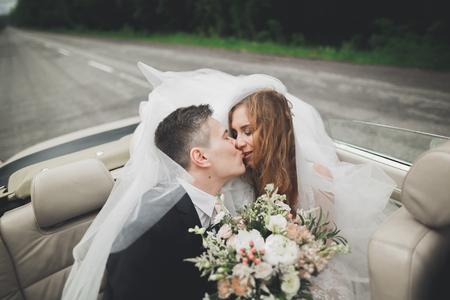 Stylish wedding couple, bride, groom kissing and hugging on retro car